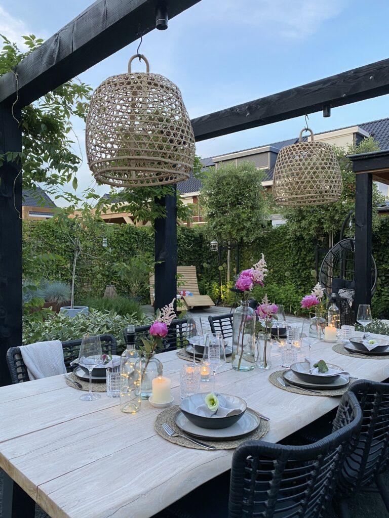 Tips voor een gezellige buitentafel: hanenmanden aan pergola